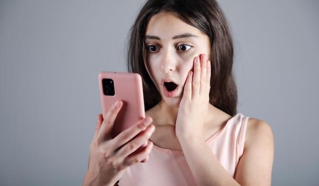 La mujer joven sorprendida que sostiene el teléfono inteligente
