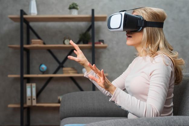 Mujer joven sorprendida sentada en el sofá en gafas 3d tratando de tocar algo invisible en el aire