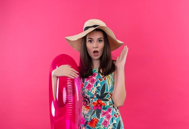 Mujer joven sorprendida con sombrero sosteniendo el anillo de natación y levantando su mano en la pared rosa aislada