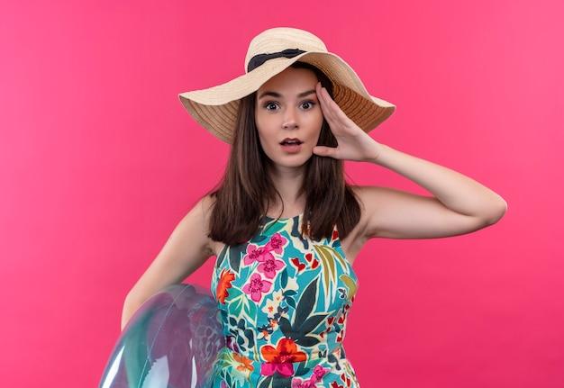 Mujer joven sorprendida con sombrero sosteniendo el anillo de natación y tocando la cara con la mano en la pared rosa aislada