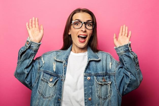 Mujer joven sorprendida sorprendida en gafas y chaqueta vaquera