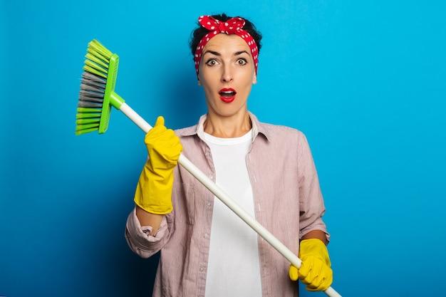 Mujer joven sorprendida sorprendida en guantes que sostienen un cepillo de limpieza en la superficie azul