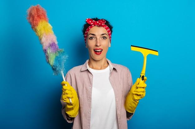 Mujer joven sorprendida sorprendida en guantes con raspador de vidrio y cepillo para polvo en la superficie azul