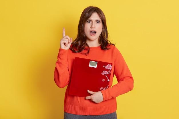 Mujer joven sorprendida sosteniendo la balanza y apuntando hacia arriba con el dedo índice, después de haber sorprendido la expresión facial, no le gusta su peso, está sorprendida y molesta.
