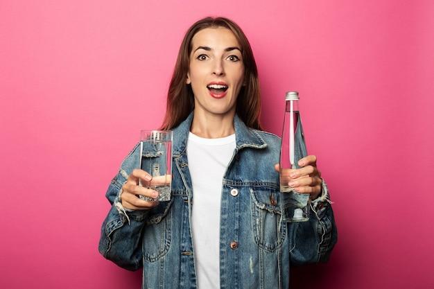 Mujer joven sorprendida sosteniendo un vaso de agua y una botella de agua