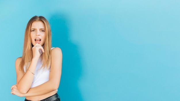 Mujer joven sorprendida con su mano en la barbilla que mira la cámara