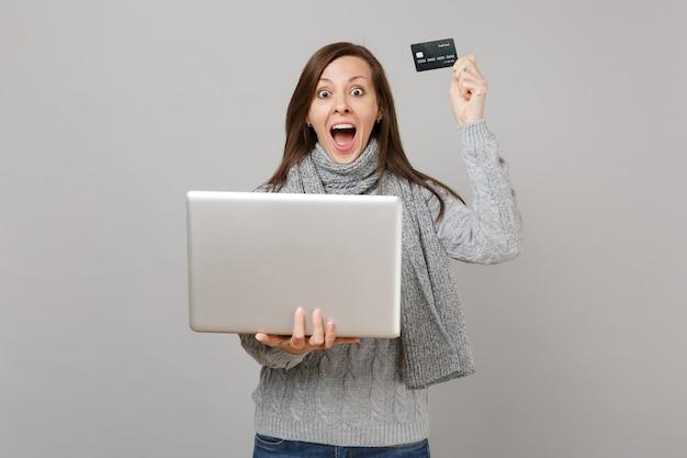 Mujer joven sorprendida en suéter, bufanda gritando, trabajando en la computadora portátil, sosteniendo la tarjeta bancaria de crédito aislada sobre fondo gris. estilo de vida saludable, tratamiento en línea consultando el concepto de estación fría.
