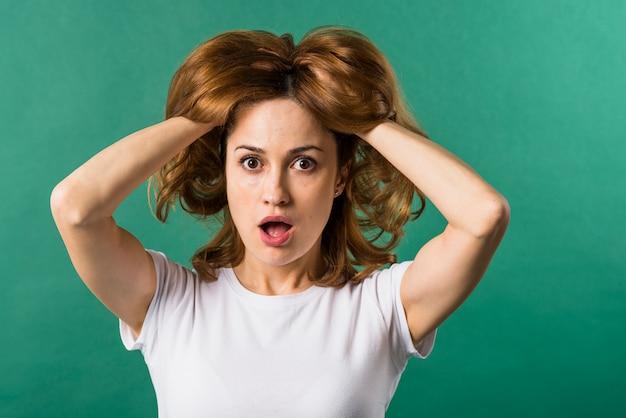 Mujer joven sorprendida con sus dos manos en pelo contra el contexto verde