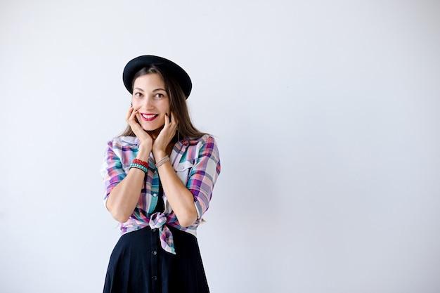 Mujer joven sorprendida tocando su rostro y sonrisa