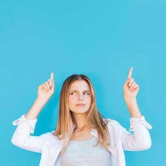 Mujer joven sospechosa que señala su dedo hacia arriba contra el fondo azul