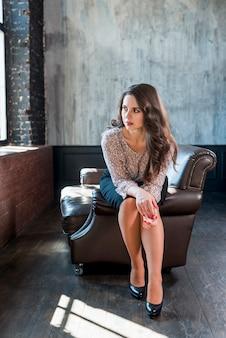Mujer joven sospechosa sentada en el borde del sillón mirando a la ventana