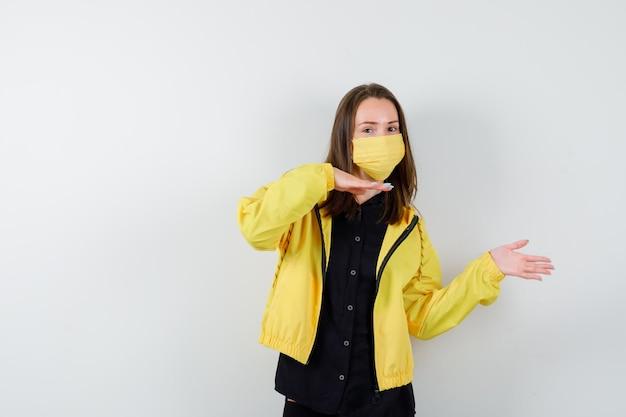 Mujer joven sosteniendo algo imaginario y apuntando a él
