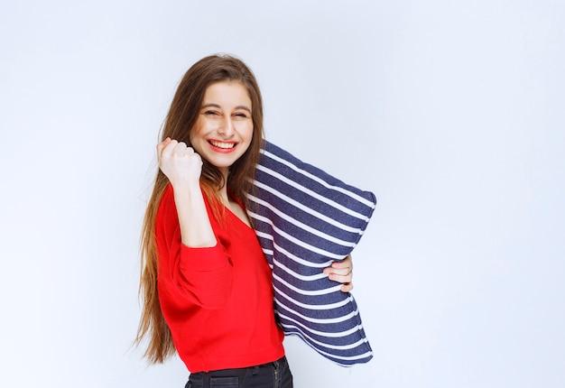 Mujer joven sosteniendo una almohada de rayas azules y sintiéndose positivo.