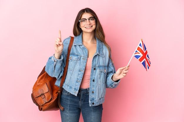 Mujer joven sosteniendo una bandera del reino unido aislada