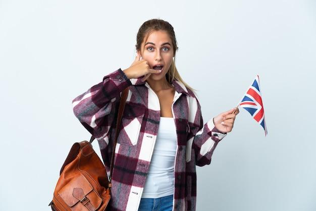 Mujer joven sosteniendo una bandera del reino unido en blanco haciendo gesto de teléfono. llámame señal