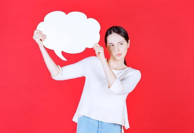 Mujer joven sosteniendo bocadillo con forma de nube