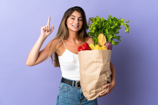 Mujer joven sosteniendo una bolsa de compras apuntando hacia una gran idea