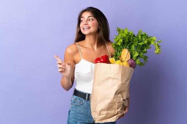 Mujer joven sosteniendo una bolsa de compras con el dedo acusador hacia el lado