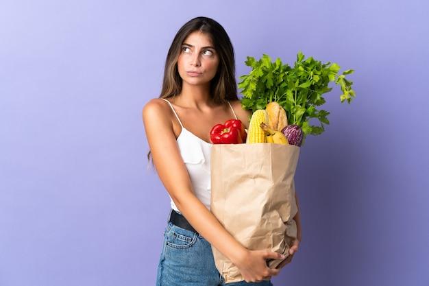 Mujer joven sosteniendo una bolsa de compras con dudas