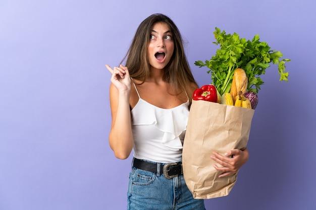 Mujer joven sosteniendo una bolsa de compras con la intención de darse cuenta de la solución mientras levanta un dedo