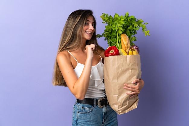 Mujer joven sosteniendo una bolsa de compras orgulloso y satisfecho de sí mismo