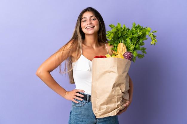 Mujer joven sosteniendo una bolsa de compras posando con los brazos en la cadera y sonriendo