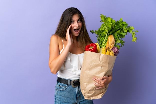 Mujer joven sosteniendo una bolsa de compras con sorpresa y expresión facial conmocionada