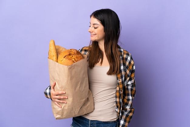 Mujer joven sosteniendo una bolsa llena de panes aislado en la pared púrpura con expresión feliz