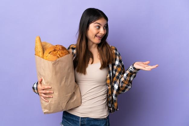 Mujer joven sosteniendo una bolsa llena de panes aislado en púrpura con expresión facial sorpresa