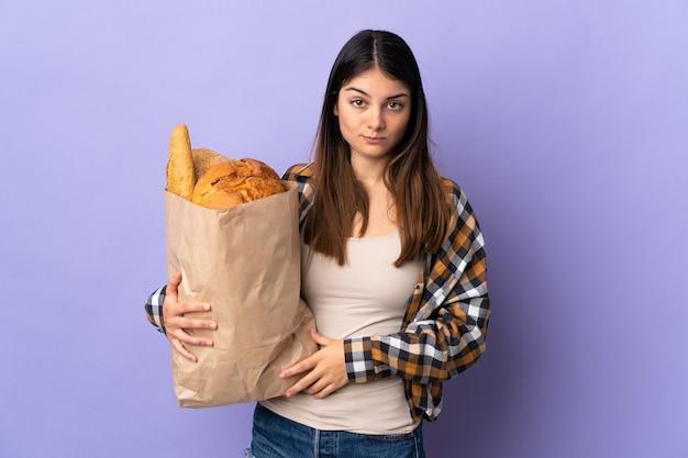 Mujer joven sosteniendo una bolsa llena de panes aislado en púrpura con expresión triste
