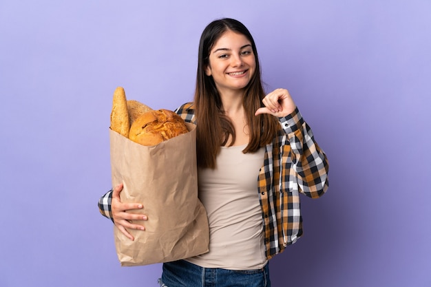 Mujer joven sosteniendo una bolsa llena de panes aislado en púrpura orgulloso y satisfecho de sí mismo