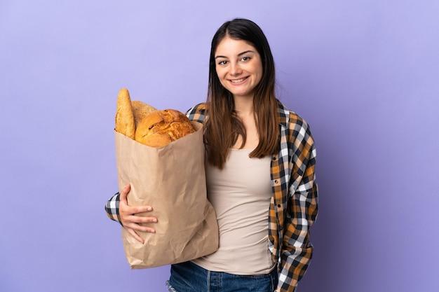 Mujer joven sosteniendo una bolsa llena de panes aislados en púrpura sonriendo mucho