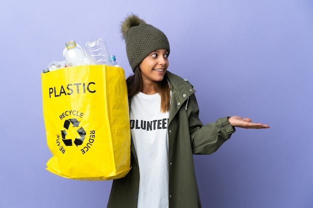 Mujer joven sosteniendo una bolsa llena de plástico con expresión de sorpresa mientras mira de lado
