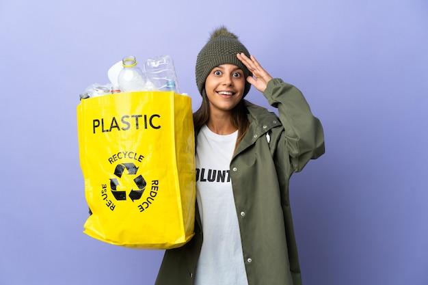 Mujer joven sosteniendo una bolsa llena de plástico con expresión de sorpresa