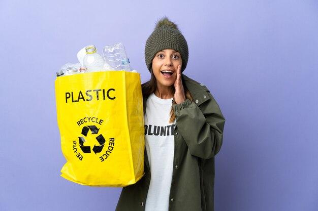 Mujer joven sosteniendo una bolsa llena de plástico con sorpresa y expresión facial conmocionada