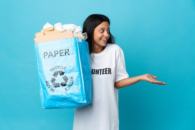 Mujer joven sosteniendo una bolsa de reciclaje llena de papel con expresión de sorpresa mientras mira de lado