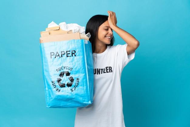 Mujer joven sosteniendo una bolsa de reciclaje llena de papel se ha dado cuenta de algo y tiene la intención de la solución