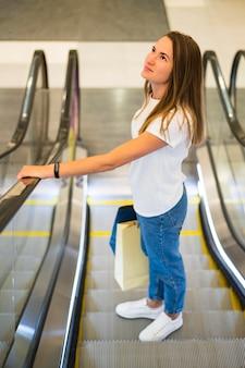 Mujer joven sosteniendo bolsas de la compra en la escalera mecánica