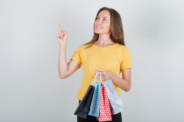 Mujer joven sosteniendo bolsas de papel con el dedo hacia arriba en camiseta amarilla, pantalón negro y mirando contento