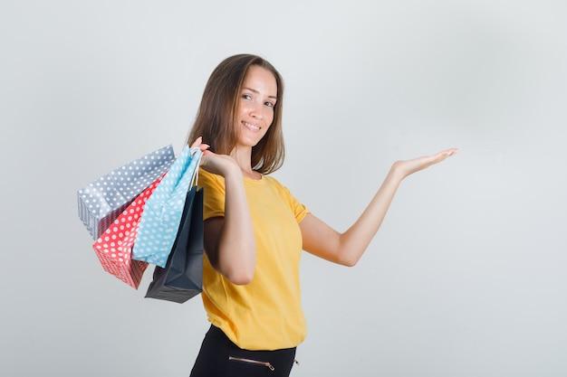 Mujer joven sosteniendo bolsas de papel con la palma abierta en camiseta amarilla