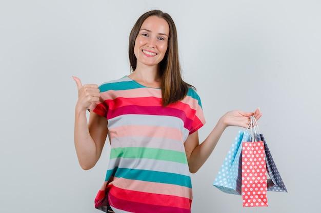 Mujer joven sosteniendo bolsas de papel con el pulgar hacia arriba en camiseta, pantalones y mirando feliz, vista frontal.