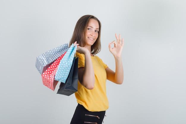 Mujer joven sosteniendo bolsas de papel con signo ok en camiseta amarilla, pantalón negro y mirando confiado.