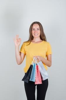 Mujer joven sosteniendo bolsas de papel con signo ok en camiseta amarilla, pantalón negro y mirando contento