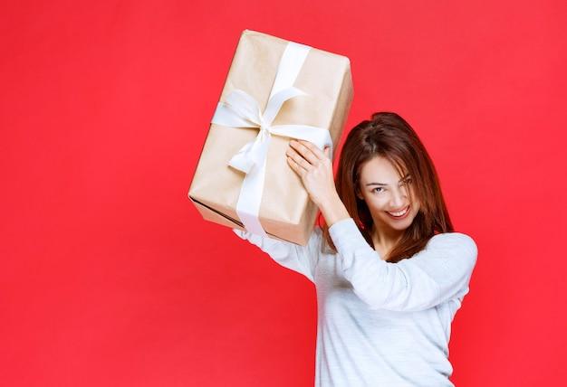Mujer joven sosteniendo una caja de regalo de cartón y parece sorprendida y positiva
