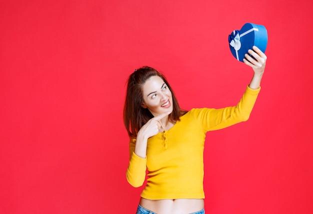 Mujer joven sosteniendo una caja de regalo con forma de corazón azul, sintiéndose positivo y feliz