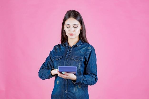 Mujer joven sosteniendo una calculadora azul en la mano y calculando