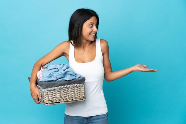 Mujer joven sosteniendo una canasta de ropa con expresión de sorpresa mientras mira de lado