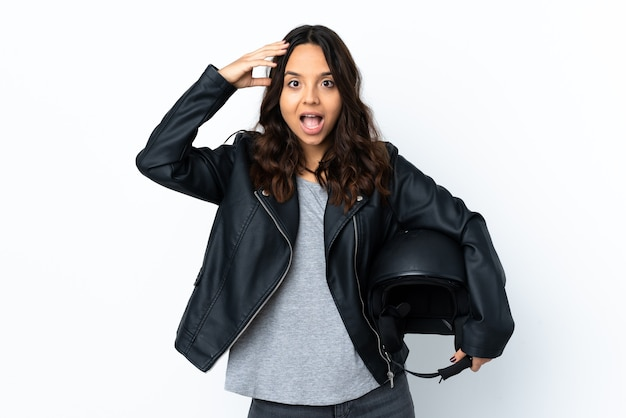 Mujer joven sosteniendo un casco de motocicleta sobre blanco aislado con expresión de sorpresa