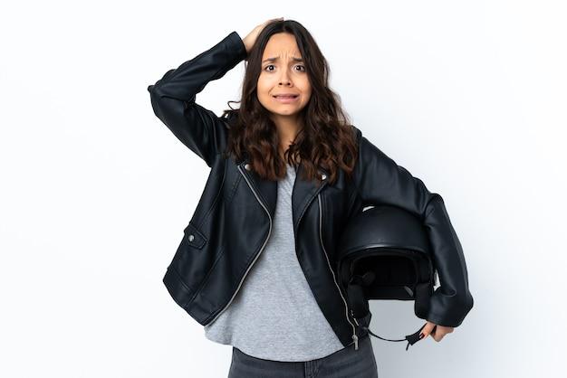 Mujer joven sosteniendo un casco de motocicleta sobre blanco aislado frustrado y toma las manos en la cabeza