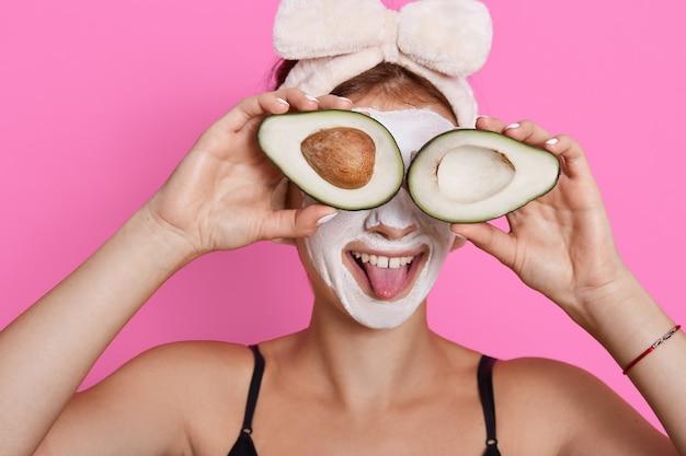 Mujer joven sosteniendo dos mitades de aguacate y cubriéndose los ojos con ella, mostrando su lengua, usando una banda para el cabello, tiene mascarilla hidratante en su rostro, divirtiéndose mientras realiza procedimientos de belleza en casa.